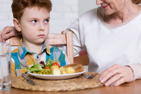 61811064 - irritated boy, sitting at a table with healthy lunch with vegetables